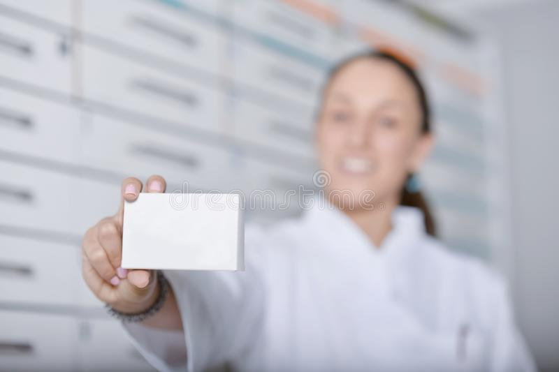 Single grinning pharmacist with white lab coat holding up a box stock photo