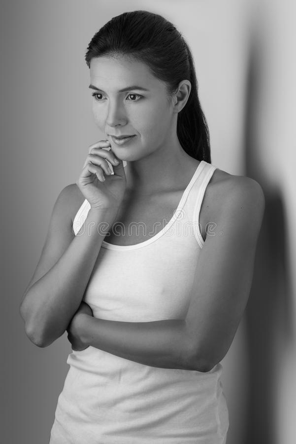 Single grinning woman with thoughtful expression. Single beautiful woman in sleeveless blouse with folded arms and hand on chin near wall in black and white royalty free stock photos