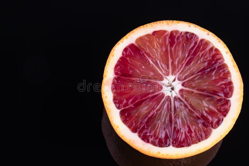 Single half of a blood orange isolated on black stock photo