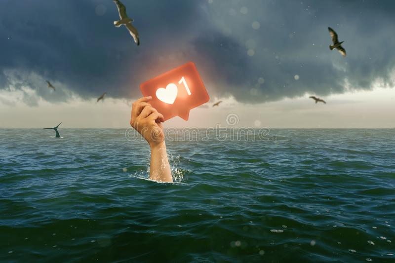 Single hand of drowning man holding Like icon stock photos