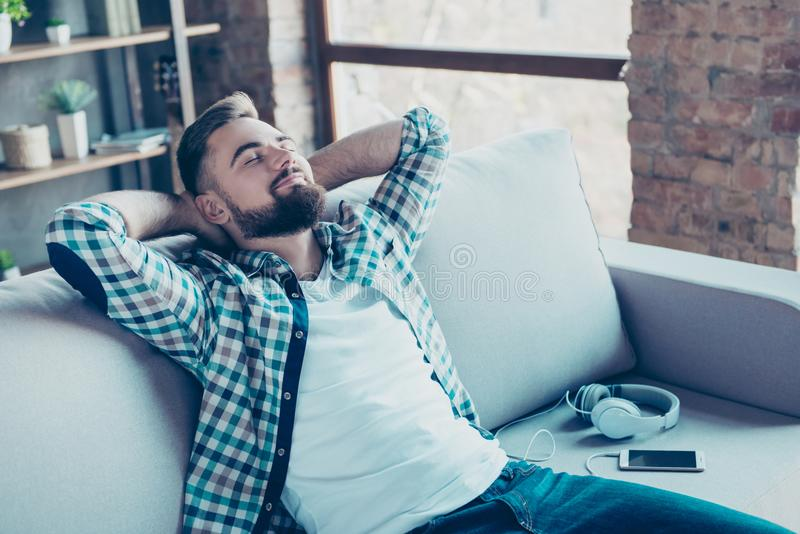 Single, happy young man in checkered shirt is relaxing on the so. Fa at home with close eyes, hands behind the head, dreaming about vacation, that is coming royalty free stock image