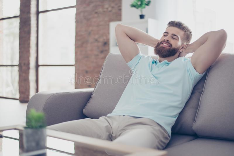 Single happy young man is relaxing on the sofa at home. He is dr. Eaming about vacation, that is coming stock image