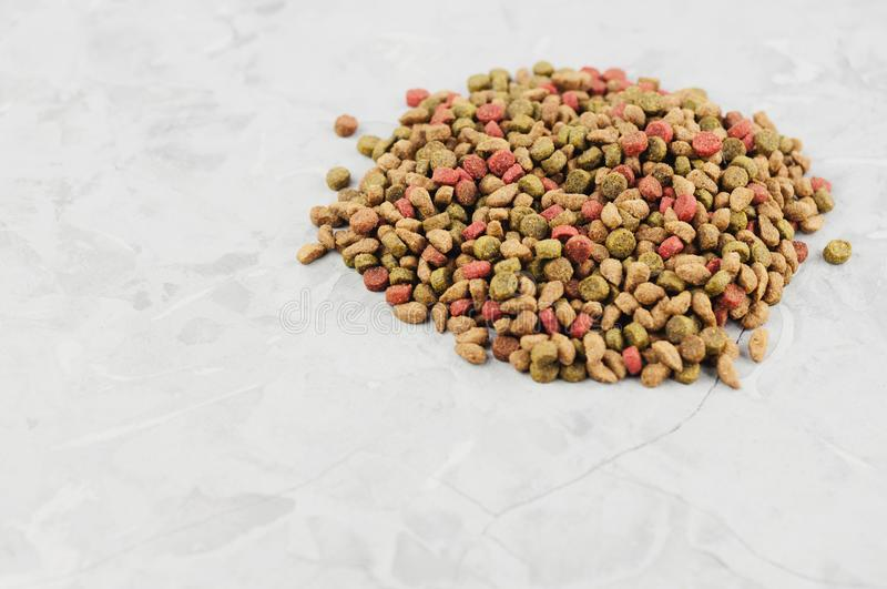 Single heap of dry coloured cat food. On old gray concrete floor royalty free stock photos