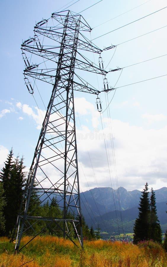 Single high tense pylon in mountains stock photography