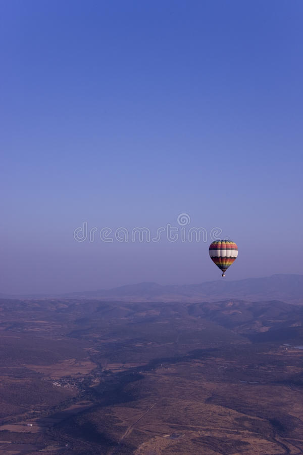 Single Hot Air Balloon Flying In Mountains Royalty Free Stock Photography