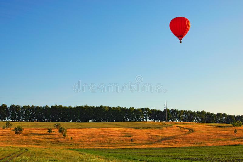 Single hot air balloon with people on the clear blue background flying over the green valley. Ksaverovka, Kyiv region, Ukraine.  royalty free stock images