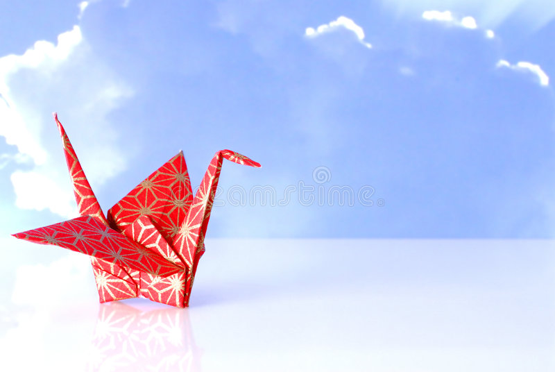 Single Japanese Peace Crane. Single red origami peace crane with reflection royalty free stock images