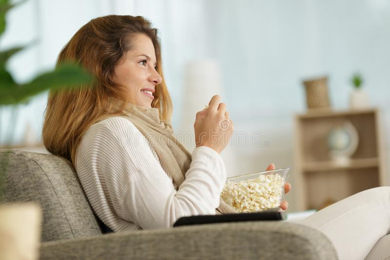 Single lady on sofa watching tv and eating popcorn. Single lady on the sofa watching tv and eating popcorn stock photos