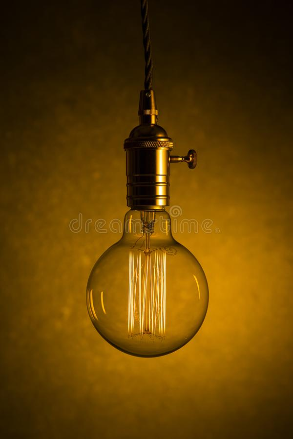 A single large filament hanging edison bulb. A single large filament illuminated hanging edison bulb against a marble background royalty free stock photos