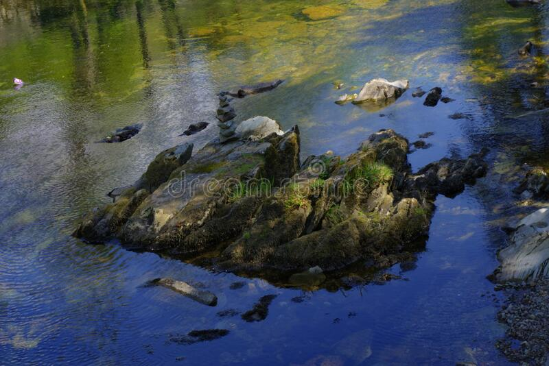 Single Large Rock in Stream. Single large rock with cairn located in slow moving shallow stream in English countryside royalty free stock image