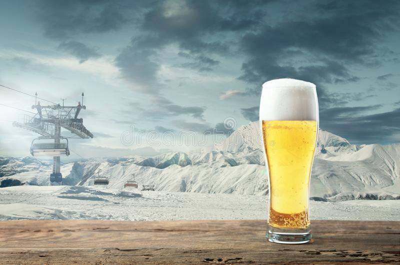 Single light beer in glass and landscape of mountains on background. Alcohole drink and snowy look and cloudly sky in front of it. Warm in winter day, holidays royalty free stock photo