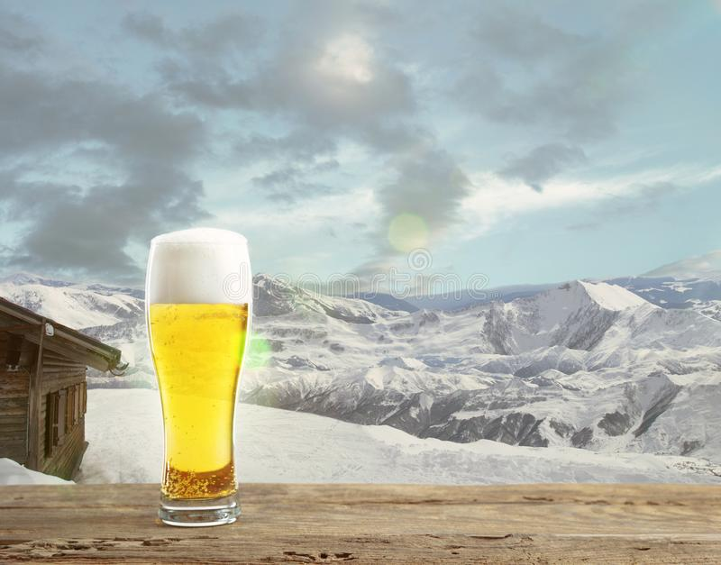 Single light beer in glass and landscape of mountains on background. Alcohole drink and sunshine look and clear sky in front of it. Warm in spring day stock image