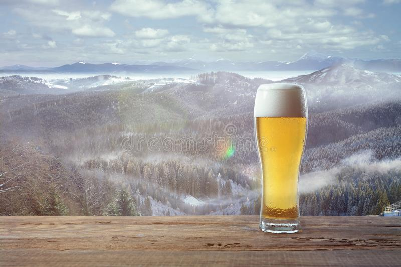 Single light beer in glass and landscape of mountains on background. Alcohole drink and sunshine look and clear sky in front of it. Warm in spring day stock images