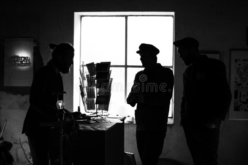 A single light bulb in focus with silhouettes of three unrecognizable men in the background stock image