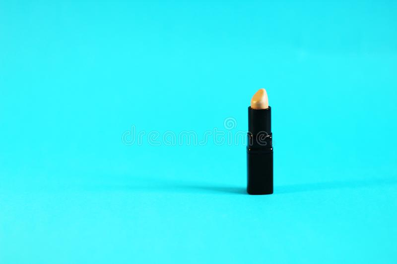 Single lipstick concept - prefect for commercials. Lipstick, Blue back ground, side view, free copy space royalty free stock images