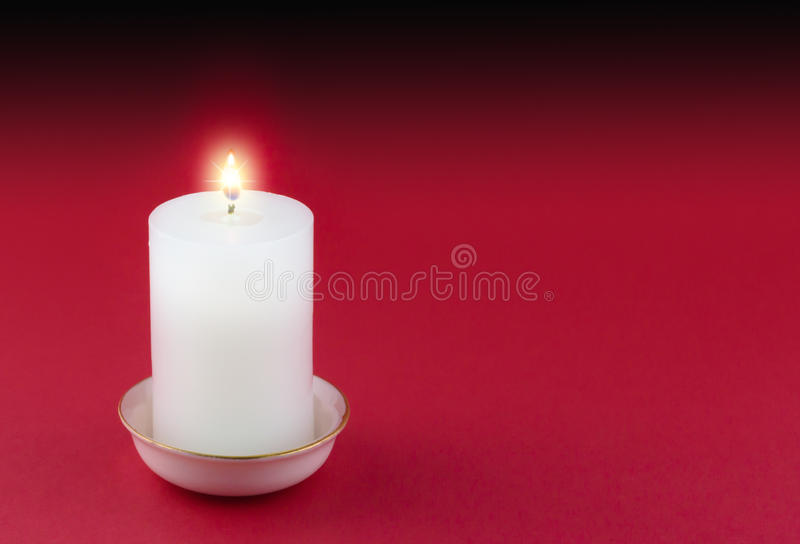 Single lit candle in gold rimmed white holder on red royalty free stock photo