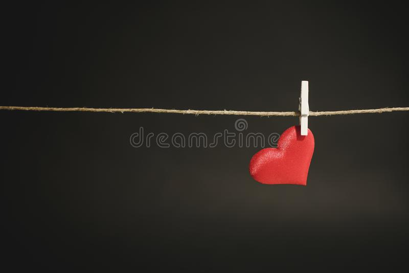 A single lonely red heart hanging from a string by white clothes peg. Romantic Valentine`s Day scene with copy space. royalty free stock photo