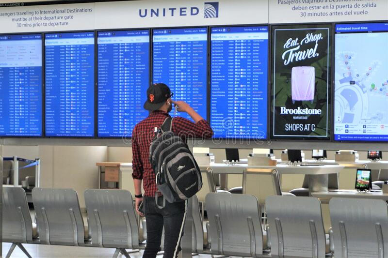 Single male traveler looking at airport departure boards royalty free stock image