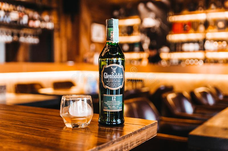 Single malt Scotch whisky in green glass bottle with whiskey and sphere ice in drinking glass on wooden table with warm and cozy. royalty free stock photo