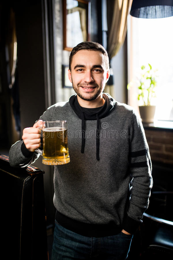 Single man in a pub or bar holding mug the beer high in the air for cheers. Single man in a pub or bar holding the beer high in the air royalty free stock photography