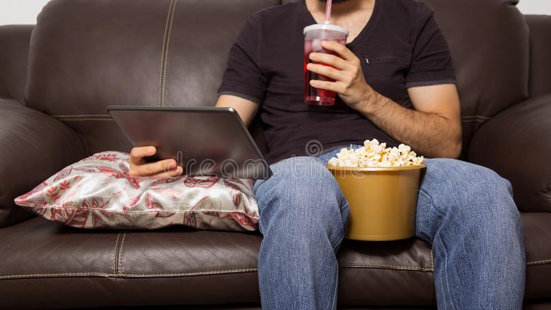 Single man watches movie on digital tablet. He is drinking juice. Single man watches movie on digital tablet. They are drinking juice and eating popcorn. Sitting royalty free stock photos