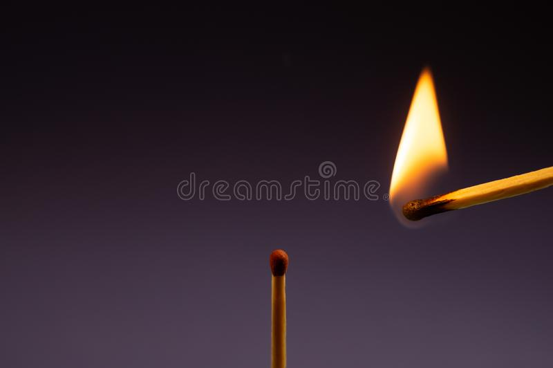 Single match and burning match nearby stock image