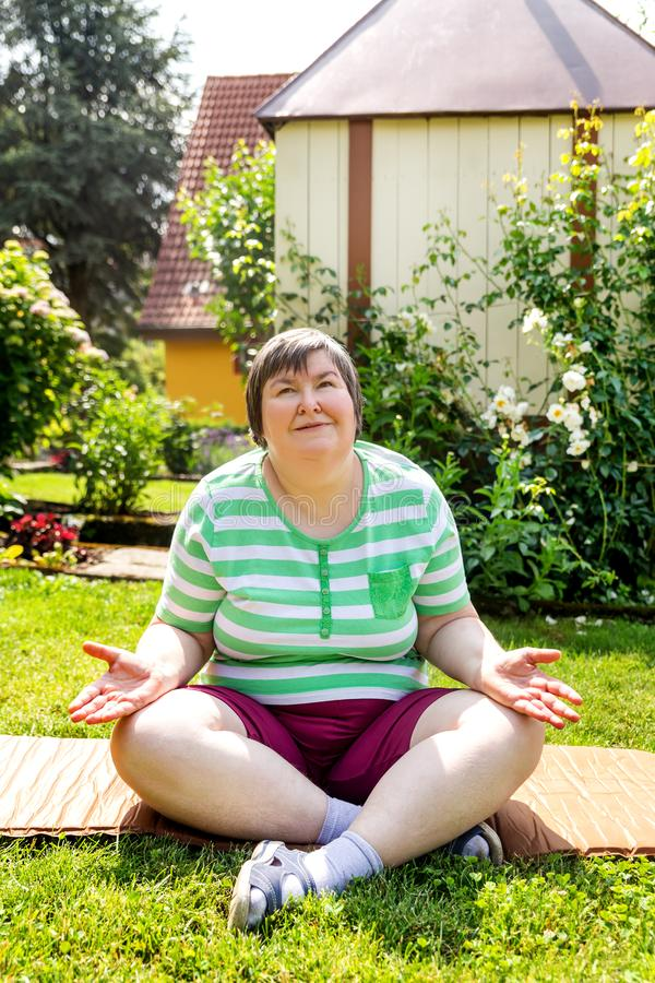 Single mentally disabled woman is doing some relaxation yoga exercises. In her garden at home royalty free stock photography