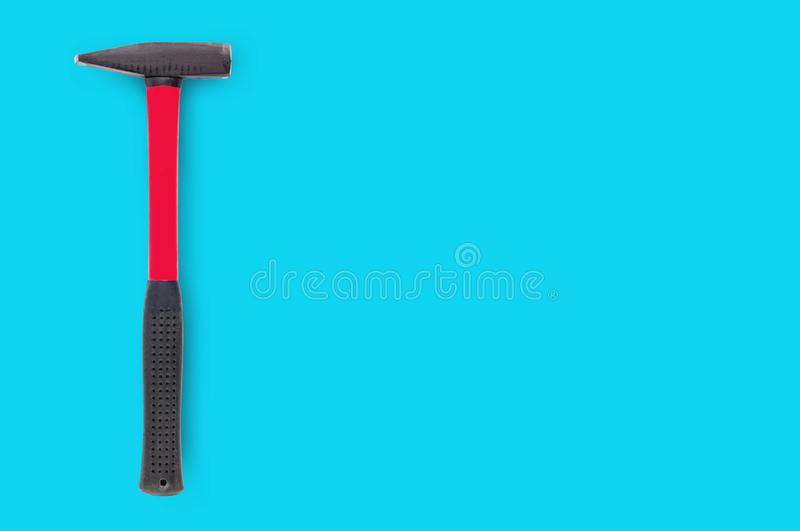 Single metal hammer with red and black rubber handle on blue background. With copy space for your text stock photography