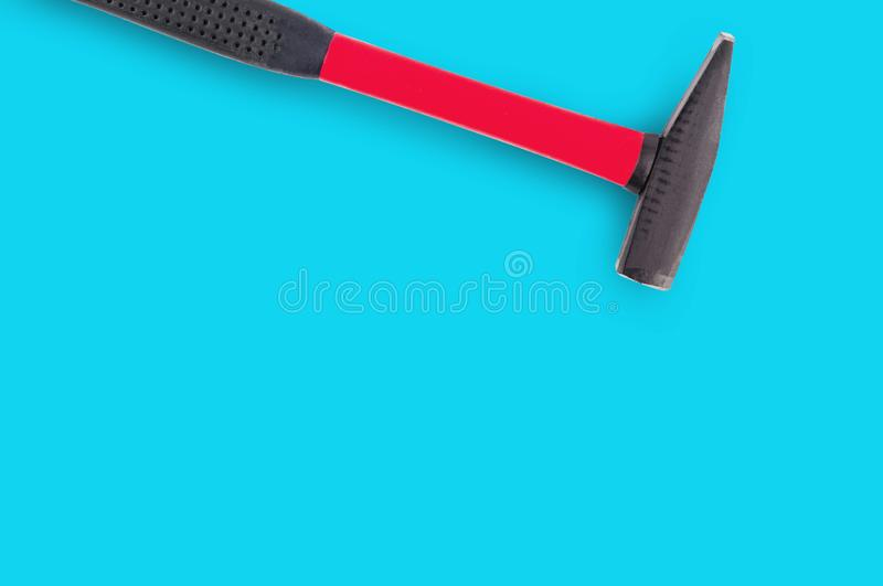 Single metal hammer with red and black rubber handle on blue background. With copy space for your text royalty free stock photos