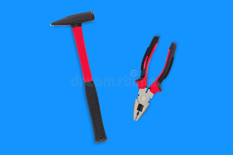 Single metal hammer with red and black rubber handle. Isolated on blue background royalty free stock photo