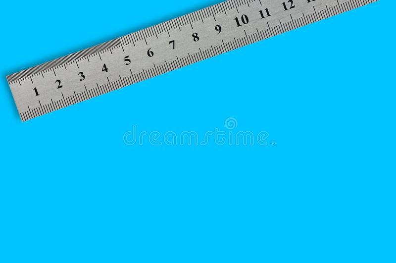 Single metal straightedge with digits and scale on blue background. With copy space for your text royalty free stock image