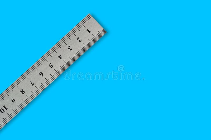 Single metal straightedge with digits and scale on blue background. With copy space for your text royalty free stock photo