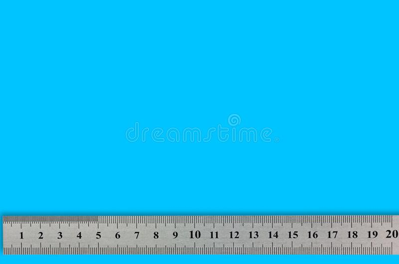 Single metal straightedge with digits and scale on blue background. With copy space for your text royalty free stock images
