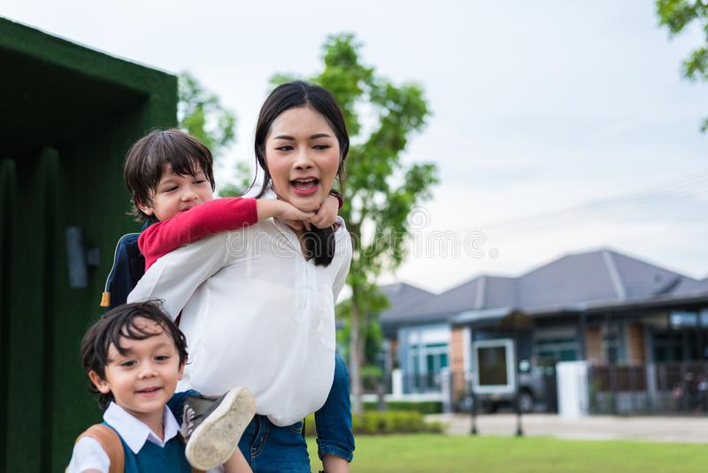 Single mom carrying and playing with her children in  garden with green wall background. People and Lifestyles concept. Happy stock image