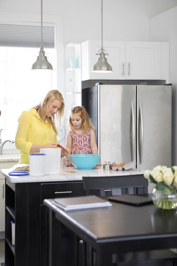 Single mom and toddler daughter baking in a modern kitchen. royalty free stock image