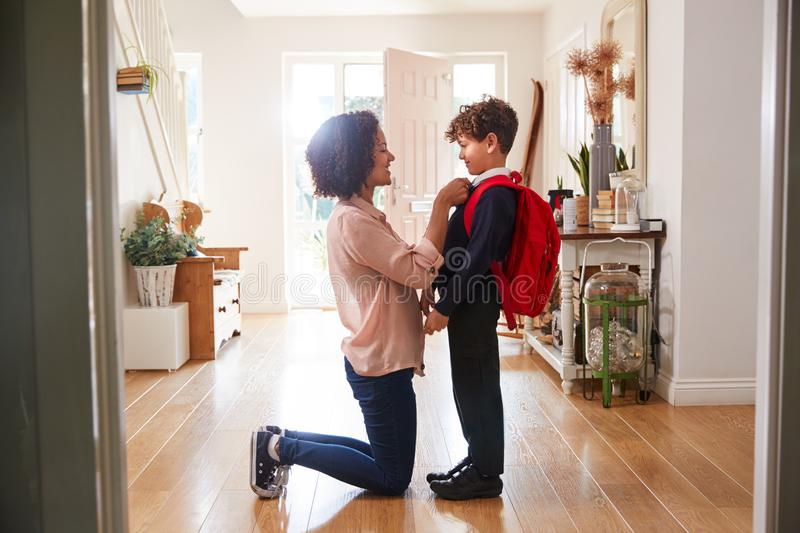 Single Mother At Home Getting Son Wearing Uniform Ready For First Day Of School royalty free stock photo