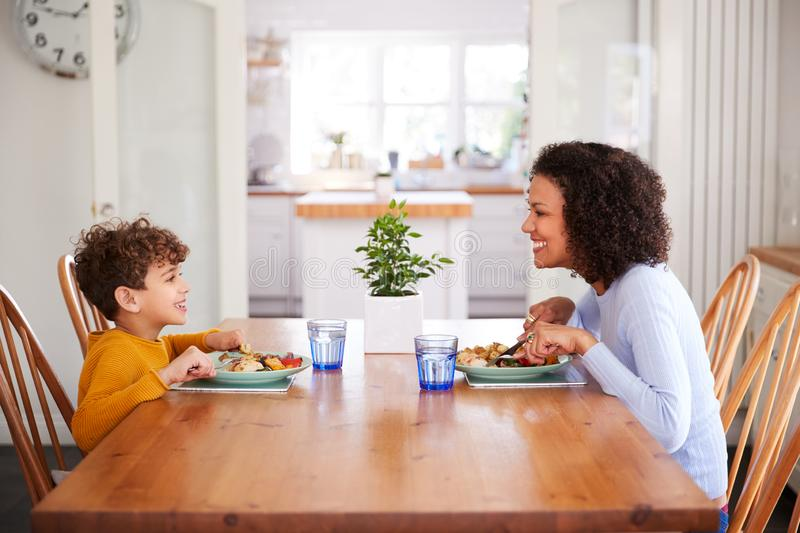 Single Mother Sitting At Table Eating Meal With Son In Kitchen At Home royalty free stock images