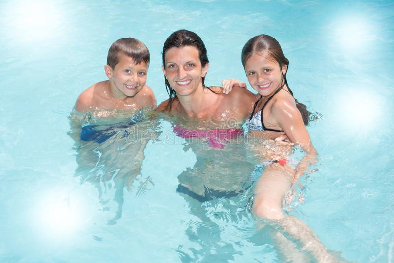 Single mother with son and daughter play in pool summer stock photos