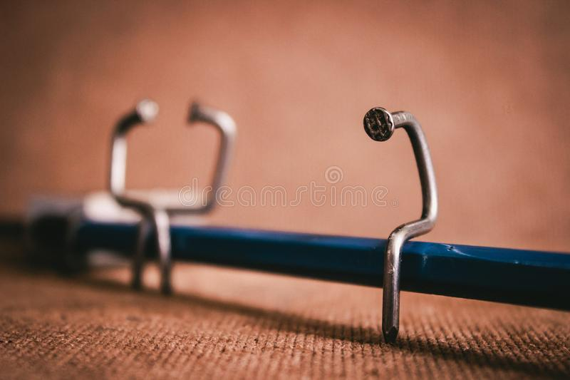 Single nail sitting on pencil bench with couple stock photo