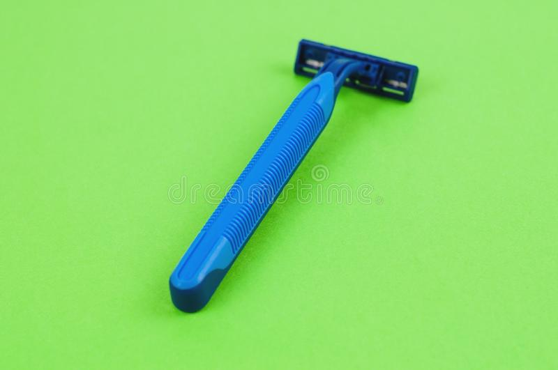 Single blue plastic disposable razor with two blades on blank green paper royalty free stock photo