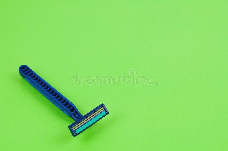 Single blue plastic disposable razor with two blades and humid strip on blank green paper stock images