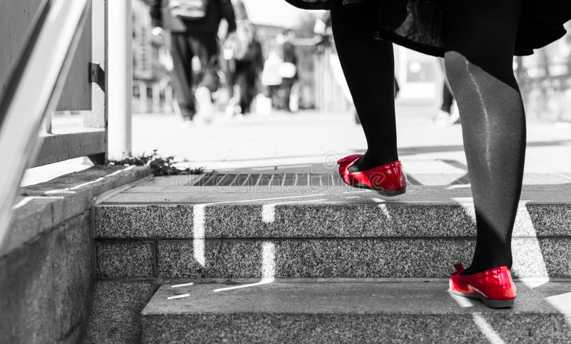 Single older woman with black tights and black dress is going upstairs with red shoes.  royalty free stock photo
