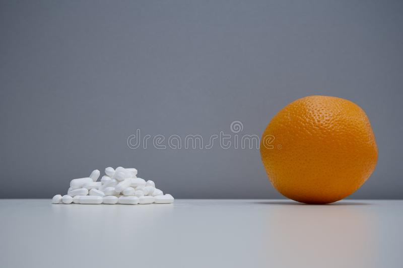 Single orange fruit with medical white pill on healthy food therapy concept grey background. Single orange fruit with medical white pill on healthy food therapy royalty free stock image