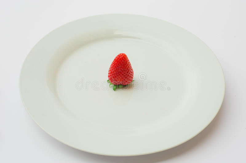 Single organic and fresh strawberry on a white plate. royalty free stock images