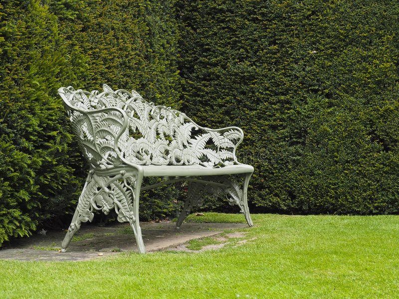Single Ornate Iron made seat or Bench in garden. Single Bench or seat made out of iron with ornate markings stock photography