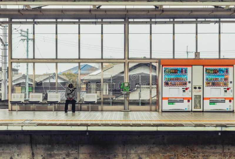 A lone waiting on an empty platform track for the next train in Japan royalty free stock photos