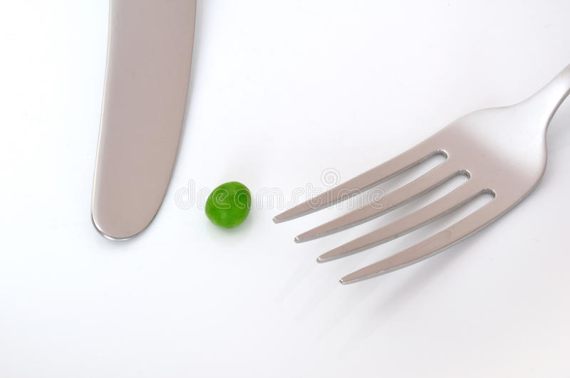 A Single Pea, a Knife, and a Fork. On a White Plate stock image