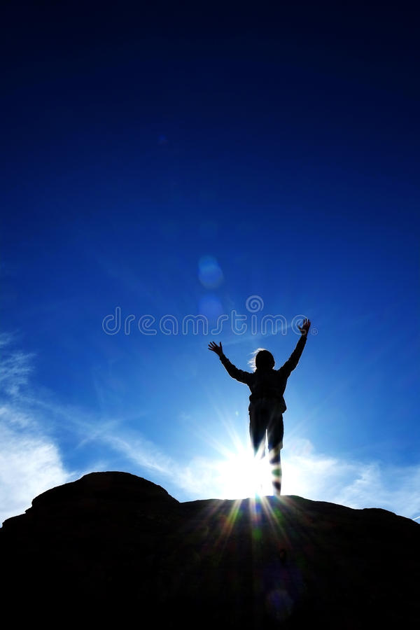 Single Person Triumphant Reaching Peak Summit on Mountain with S. Single person triumphantly reaching peak summit of mountain with sky and sunlight silhouette stock photography