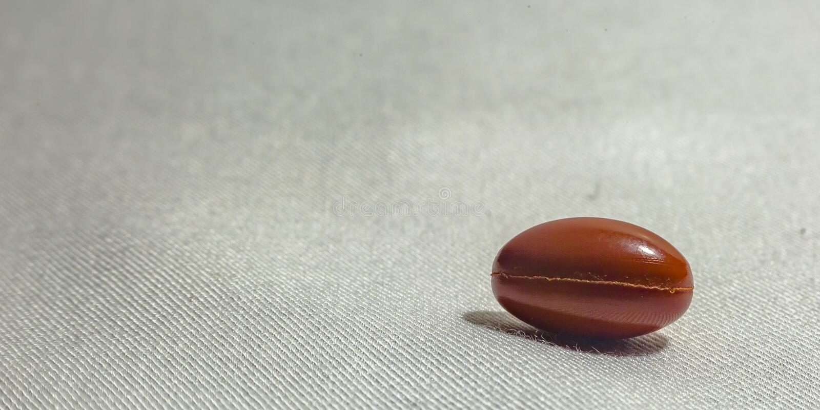 Single pill on a white fiber texture background. Close up shot of single pill agianst a white background with a fiber texture. The orange pill has an oblong stock image