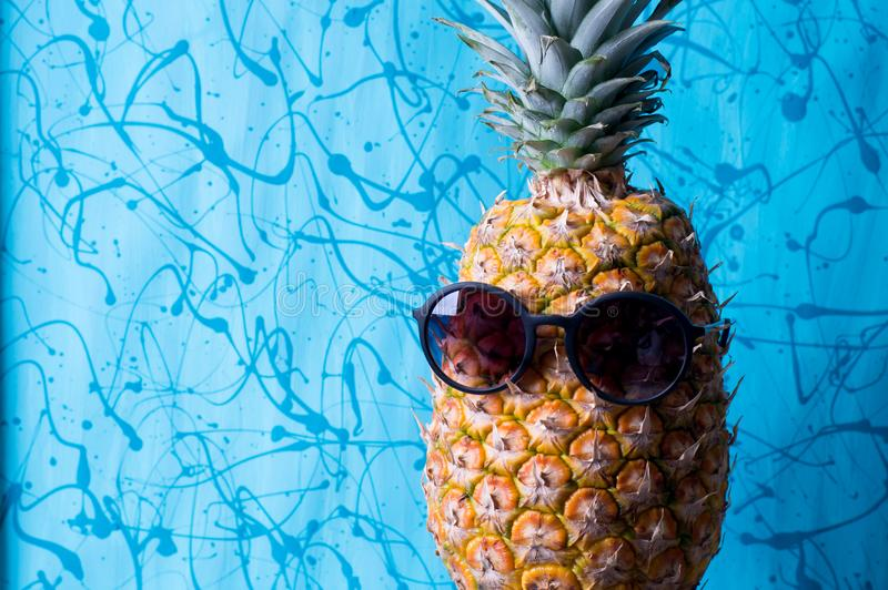 Impotent pineapple with sunglasses. Single pineapple with sunglasses on a blue abstract background royalty free stock images